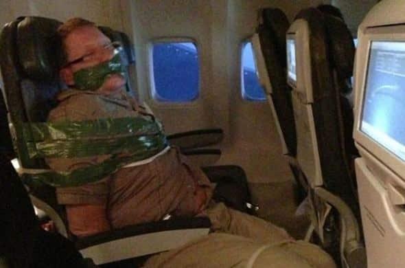 Pasażer samolotu zakneblowany i związany taśmą.
